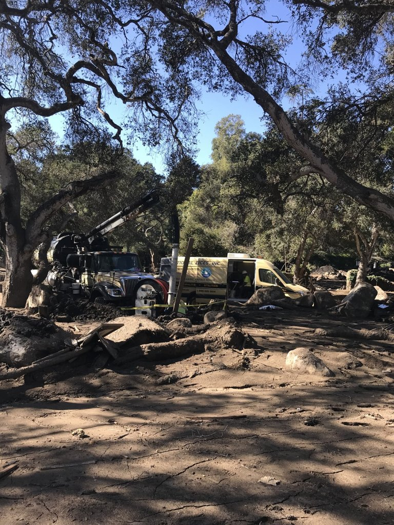 Two National Plant trucks at mudslide cleanup site in Montecito